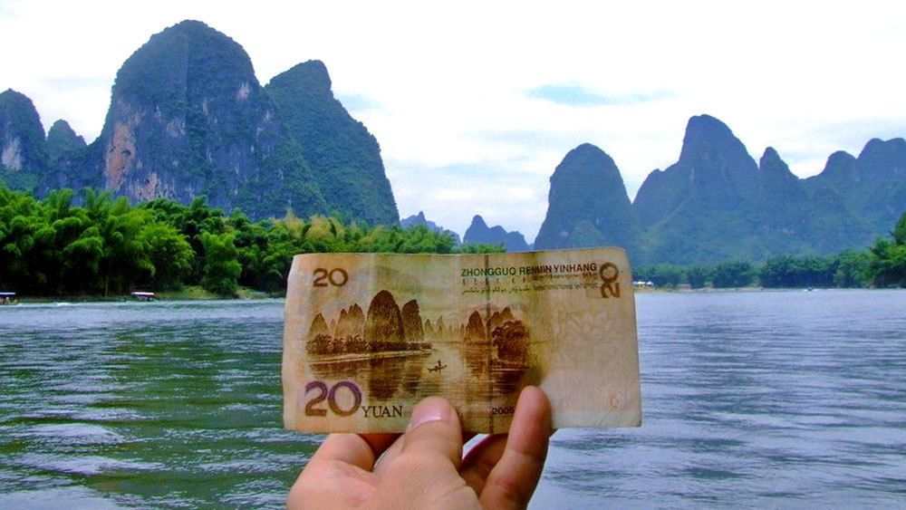 visitor holding up Chinese currency at Guilin