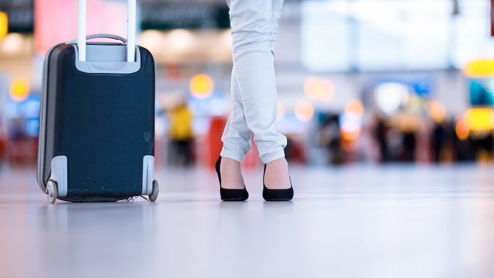 Woman standing with her carry on luggage at the airport in the British Virgin Islands