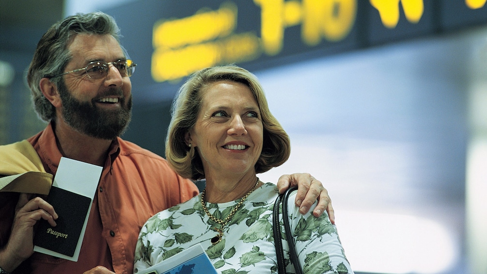 Couple smiling while holding their passports in the airport in the British Virgin Islands