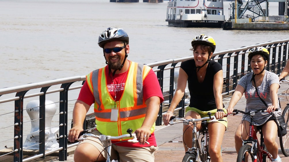 Show item 3 of 4. Bicycling group riding along the water in New Orleans