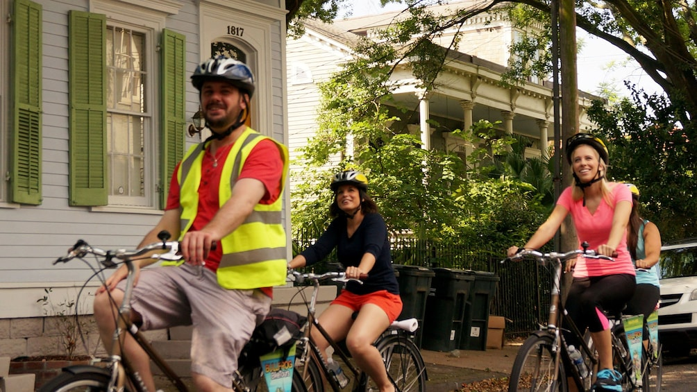 Show item 1 of 4. Bicycling group with guide riding through the streets of New Orleans