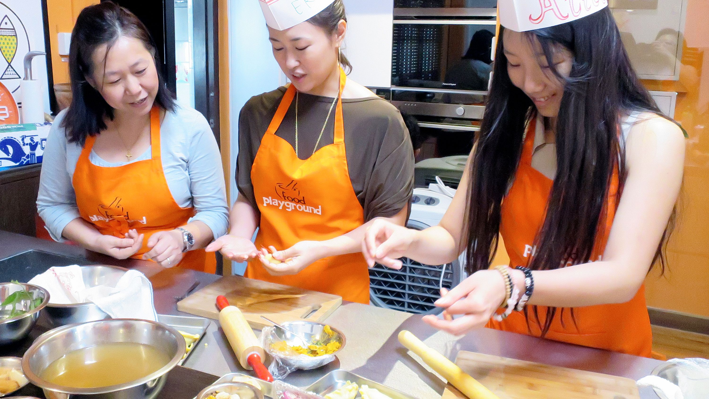 Close view of three ladies making cultural dishes in Singapore