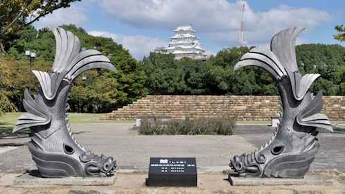 Pair of fish sculptures with Himeji Castle in the background in Japan