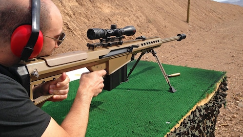 man steadying a sniper rifle at an outdoor shooting range in Las Vegas