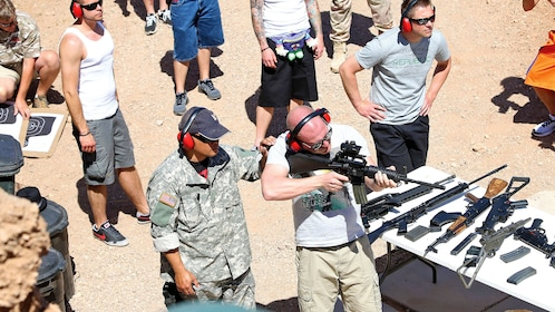 men testing out various assault weapons at an outdoor shooting range in Las Vegas