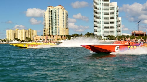 A red and yellow speedboat power thorough the water off of Miami