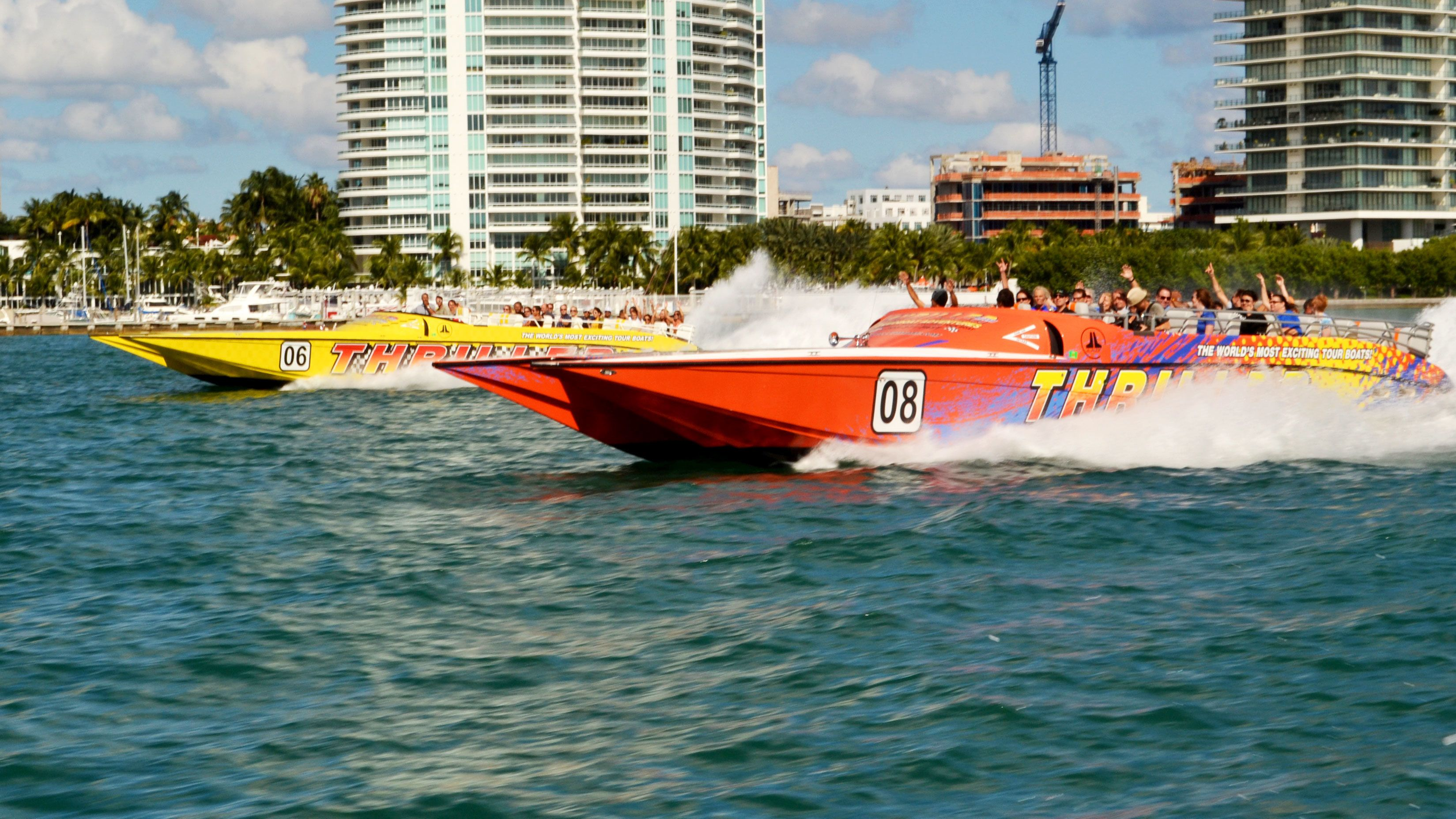 Two speedboats full of people roar through the ocean off Miami