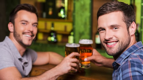 Couple of guys toasting with pints of beer in Baltimore