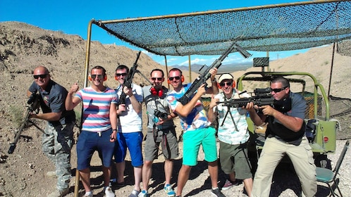 group of men holding rifles at an outdoor shooting range in Las Vegas