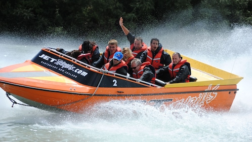 Jet boat full of people cuts through the water with large wake