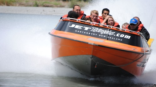 Jet boat full of people cruises through the water