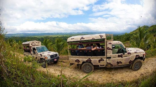 trucks with people riding in the back on the trail in jamaica