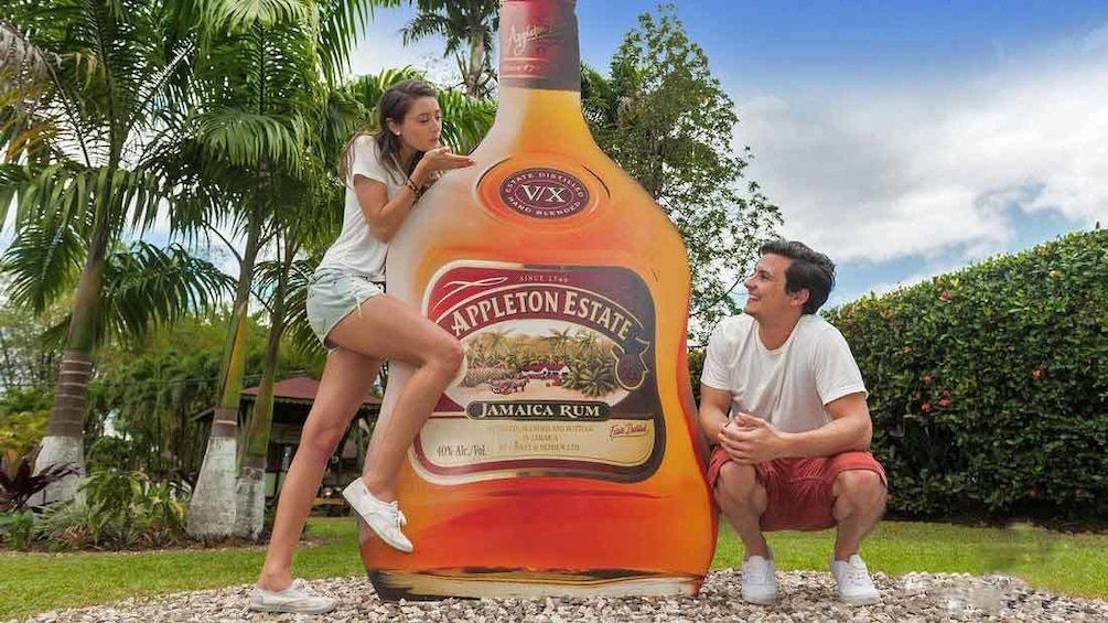 Show item 1 of 7. friends posing with giant rum bottle in jamaica