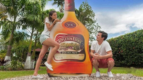 friends posing with giant rum bottle in jamaica
