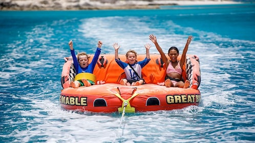 Kids on the floating raft being pulled by the boat on the private charter tour in the Turks and Caicos