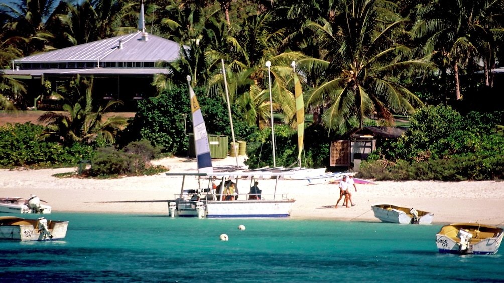 Show item 3 of 4. Boats anchored off the shoreline in blue waters in Lizard island