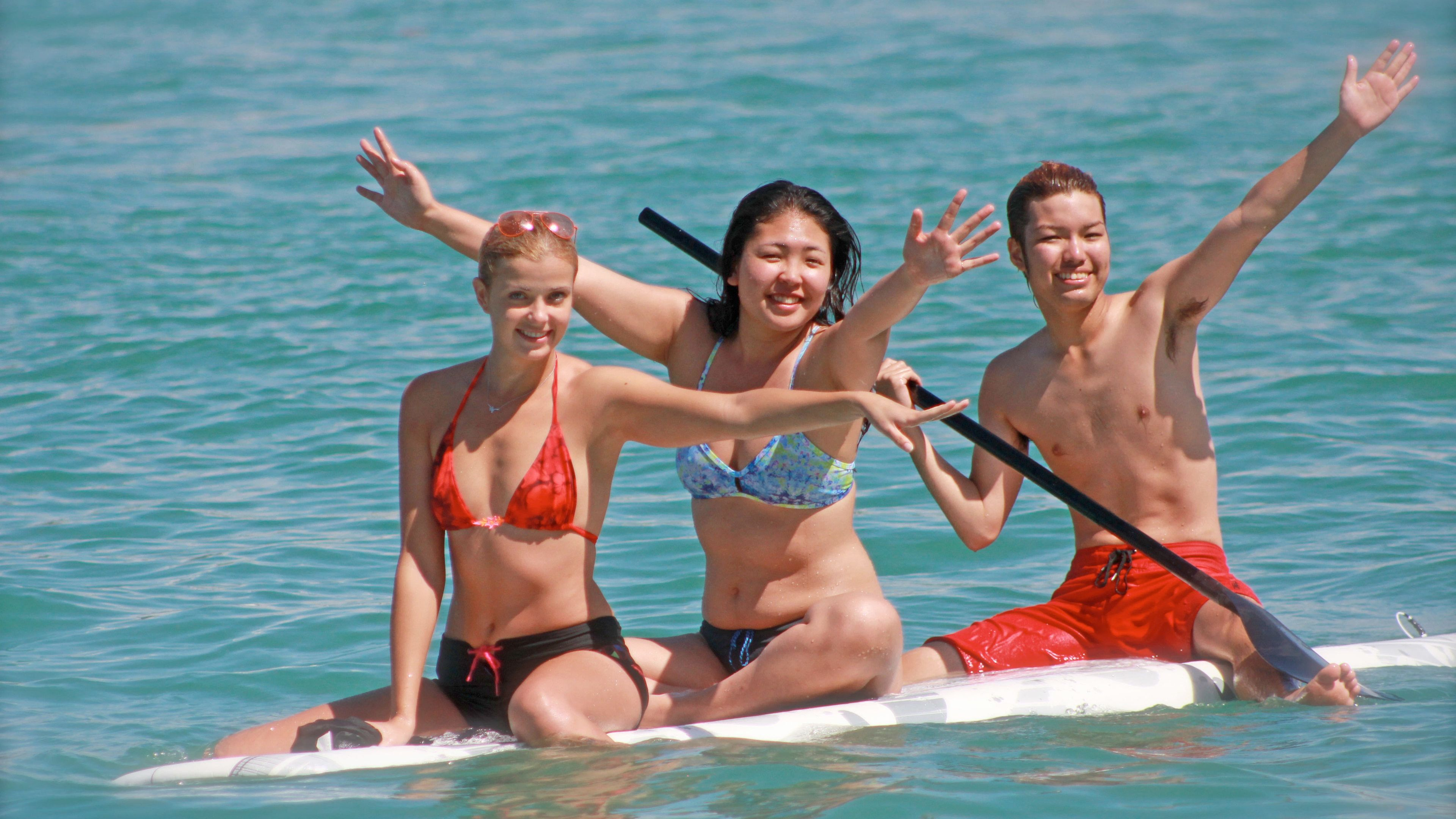 Three guests having a good paddle boarding time on Miami Beach