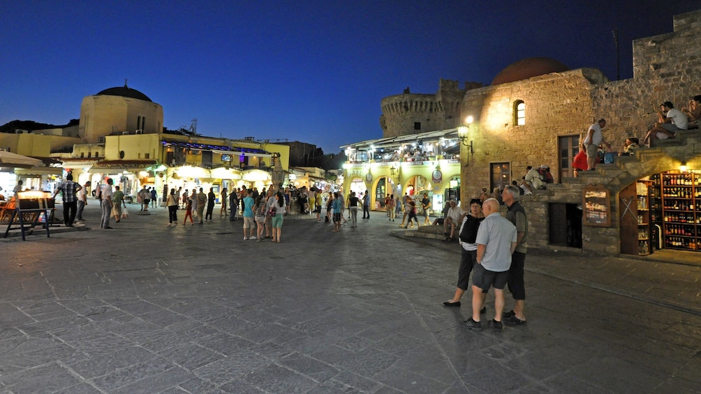 Åpne bilde 2 av 5. A Grecian plaza with storefronts and patrons at night
