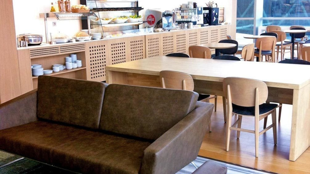 Show item 2 of 4. A leather couch and tables with chairs at the Izmir International Comfort Lounge