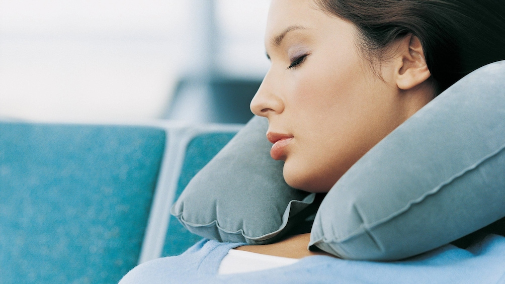 Show item 3 of 4. A woman falling asleep with an inflatable neck rest