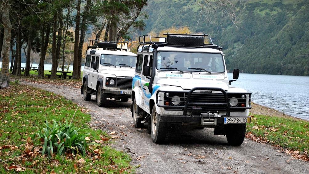 Two jeeps drive down dirt road in Sete Cidades Half-Day Safari