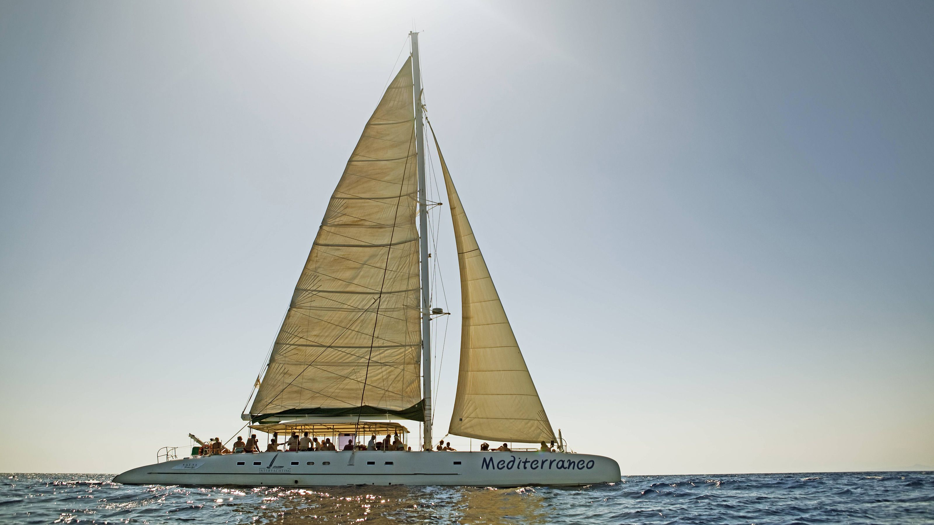 A Catamaran with its sail illuminated by the sun