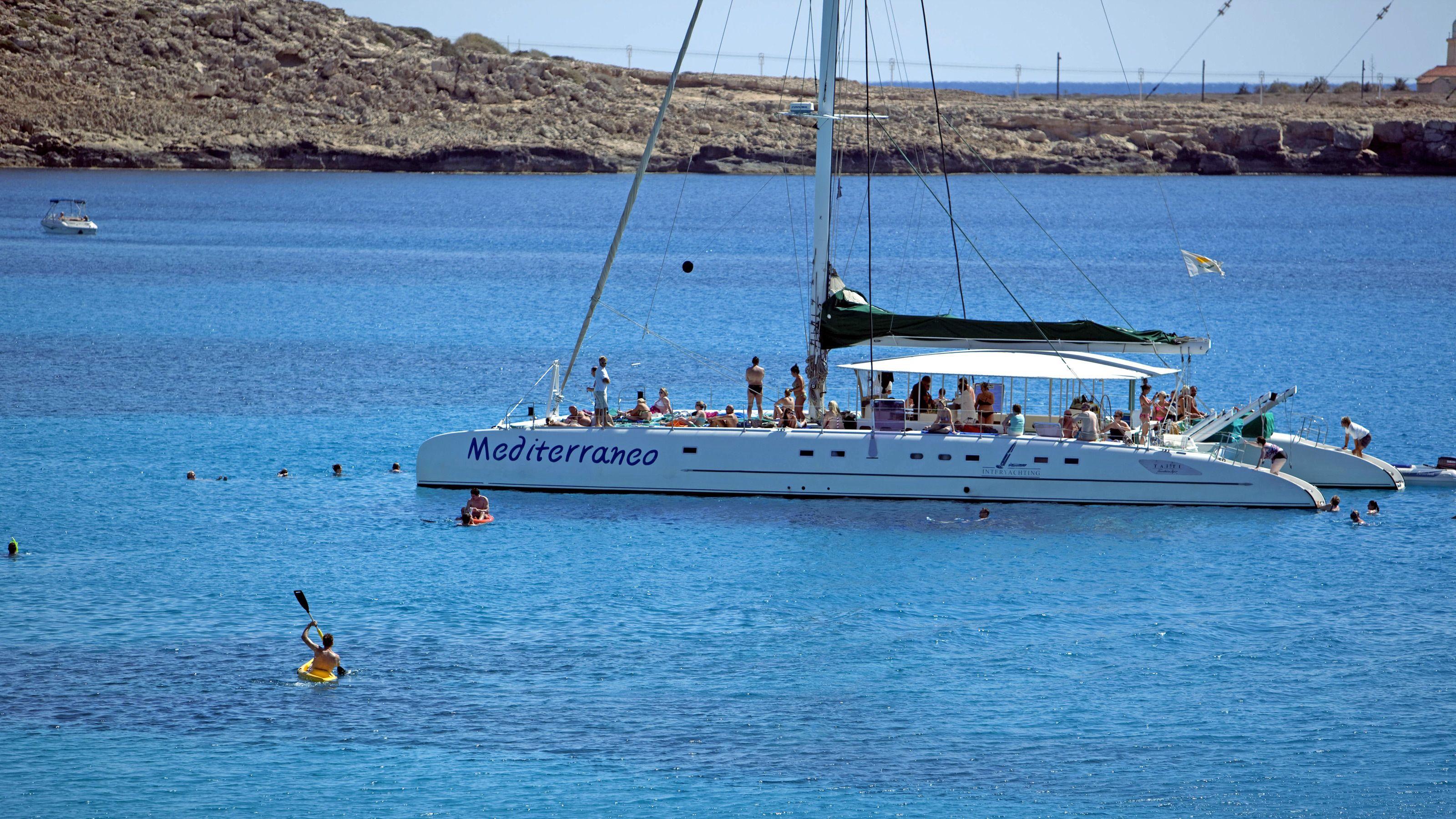 Kayakers paddle around an anchored catamaran full of people