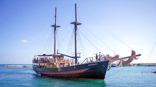 A pirate ship anchored with sails down