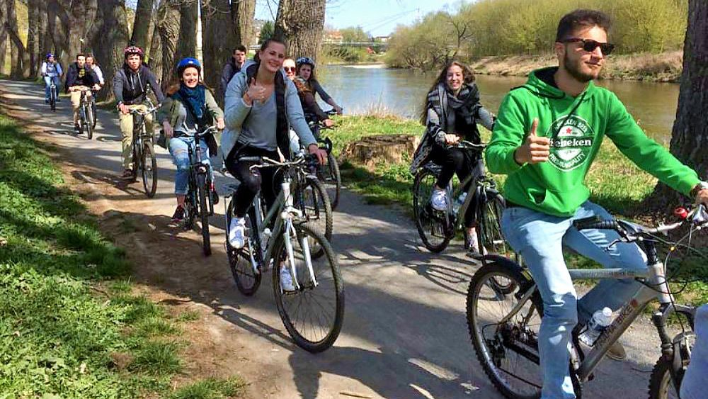 Group rides bike next to water on a concrete path.