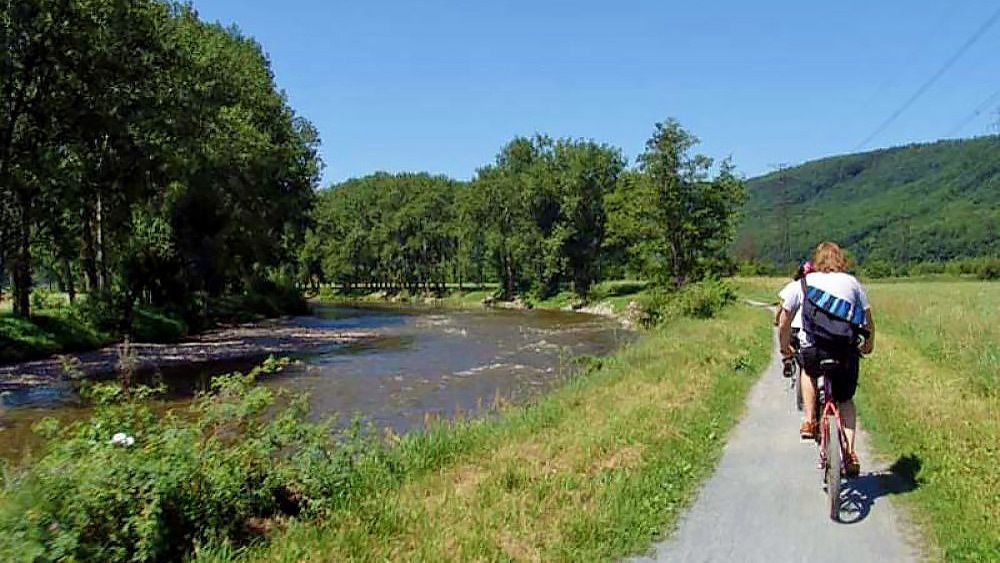 Bikers ride path next to river in wooded hillside