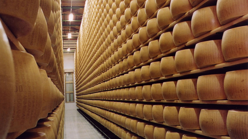 Show item 3 of 7. Racks of wheels of Parmesan cheese being aged