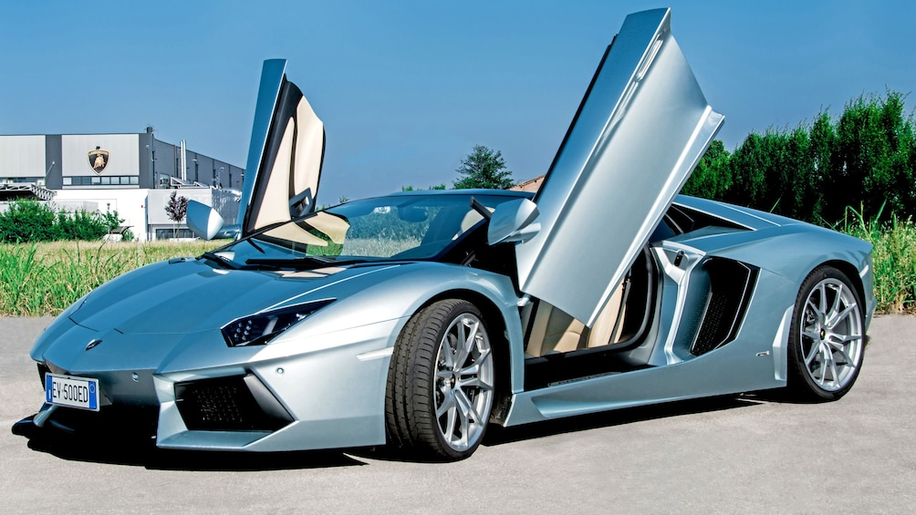 Show item 5 of 5. A Lamborghini outside with doors raised.