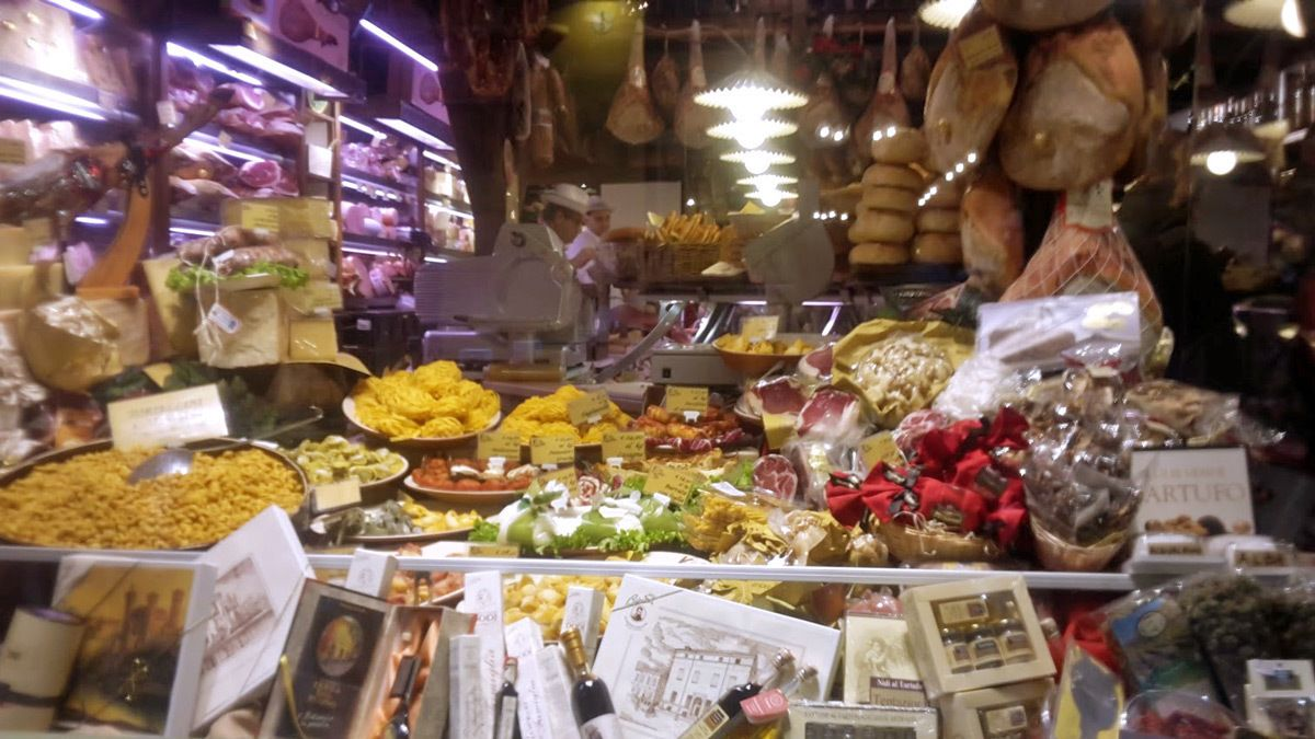 A grocery store front window with pasta, cheese and meat on display