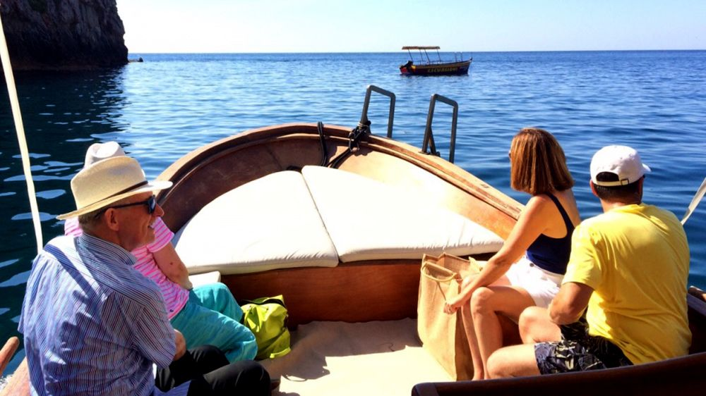 Four people sit on a boat during Taormina Boat Tour