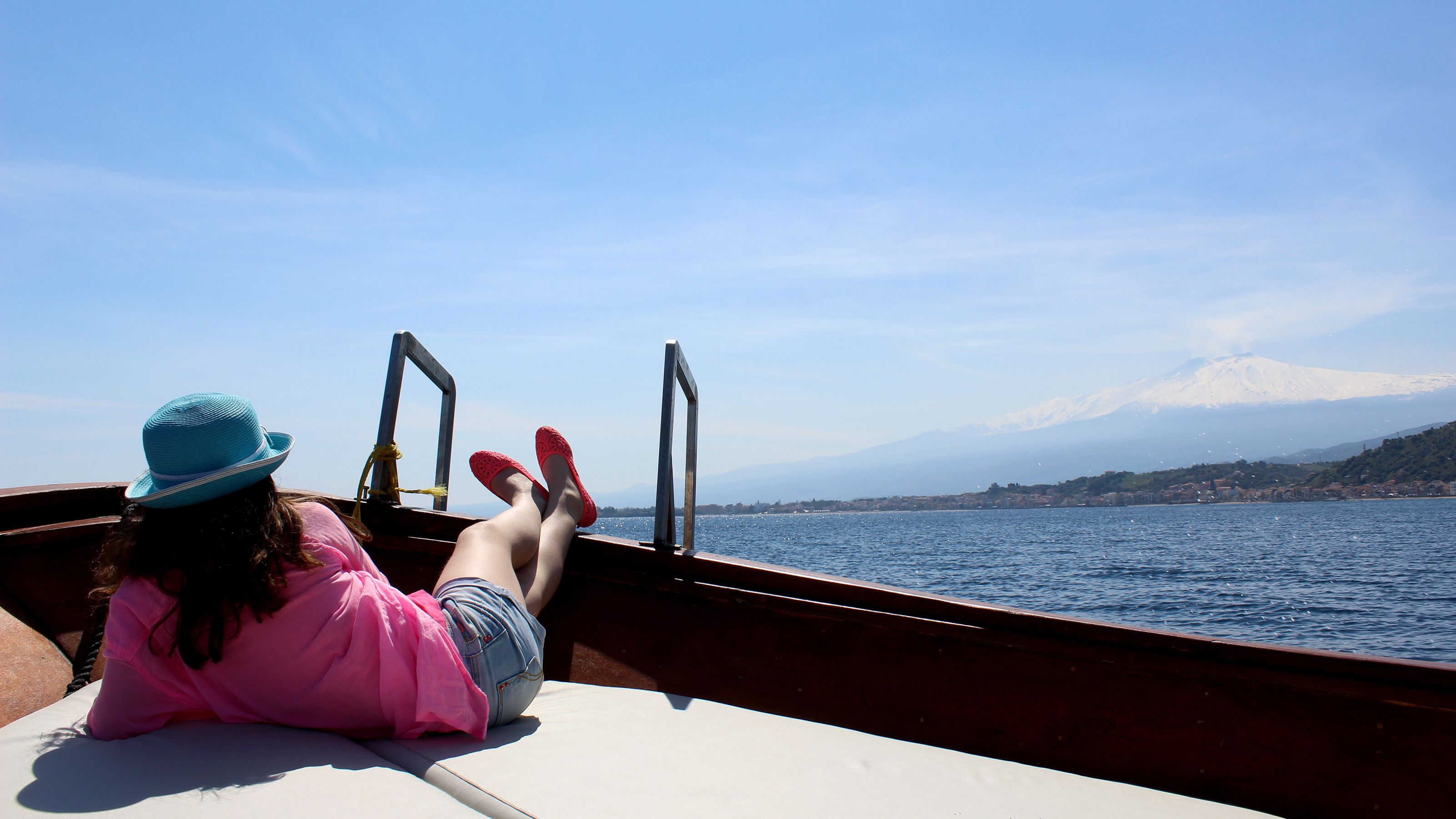 Woman lounges on deck of boat during Taormina Boat Tour