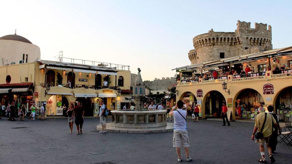 Tourist takes picture in Grecian town square.