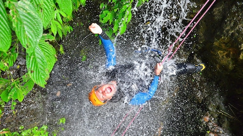 Rock climber is suspended by ropes and is hit by water from a waterfall