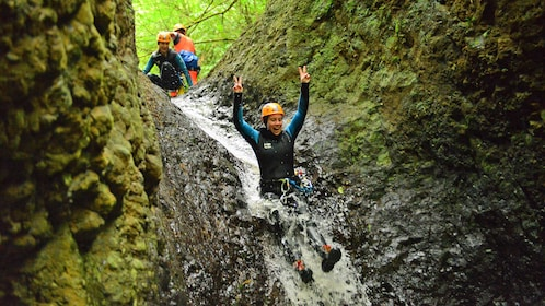Woman holds up peace signs while sliding down waterfall