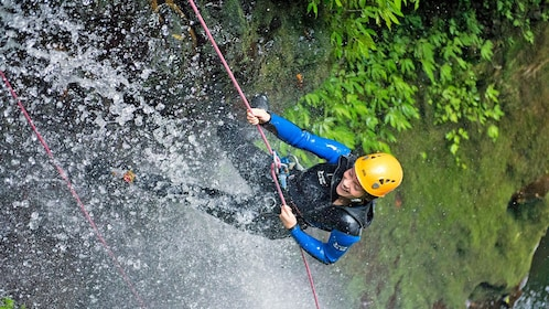 Climber descends a rope next to a waterfall