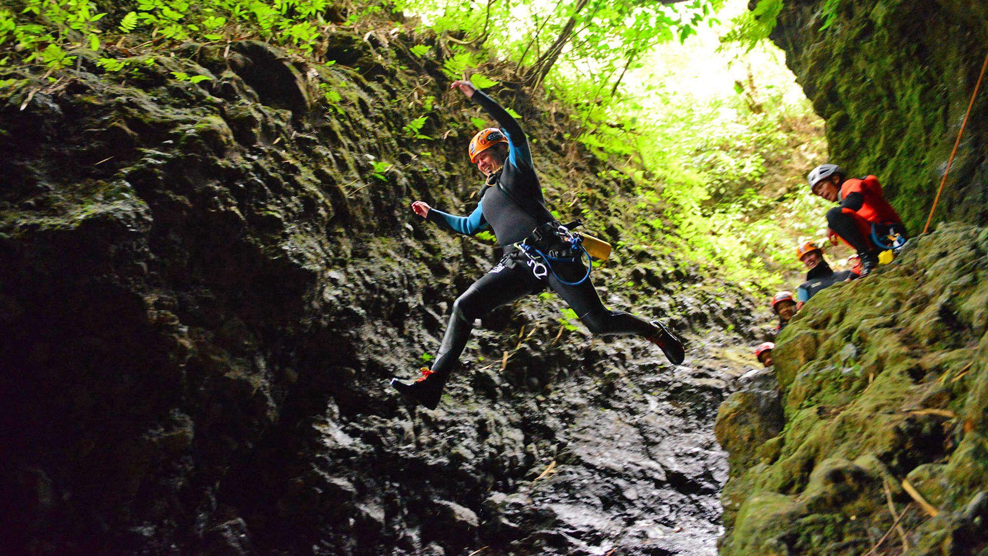 Rock climber jumps down a cliff into a pool below