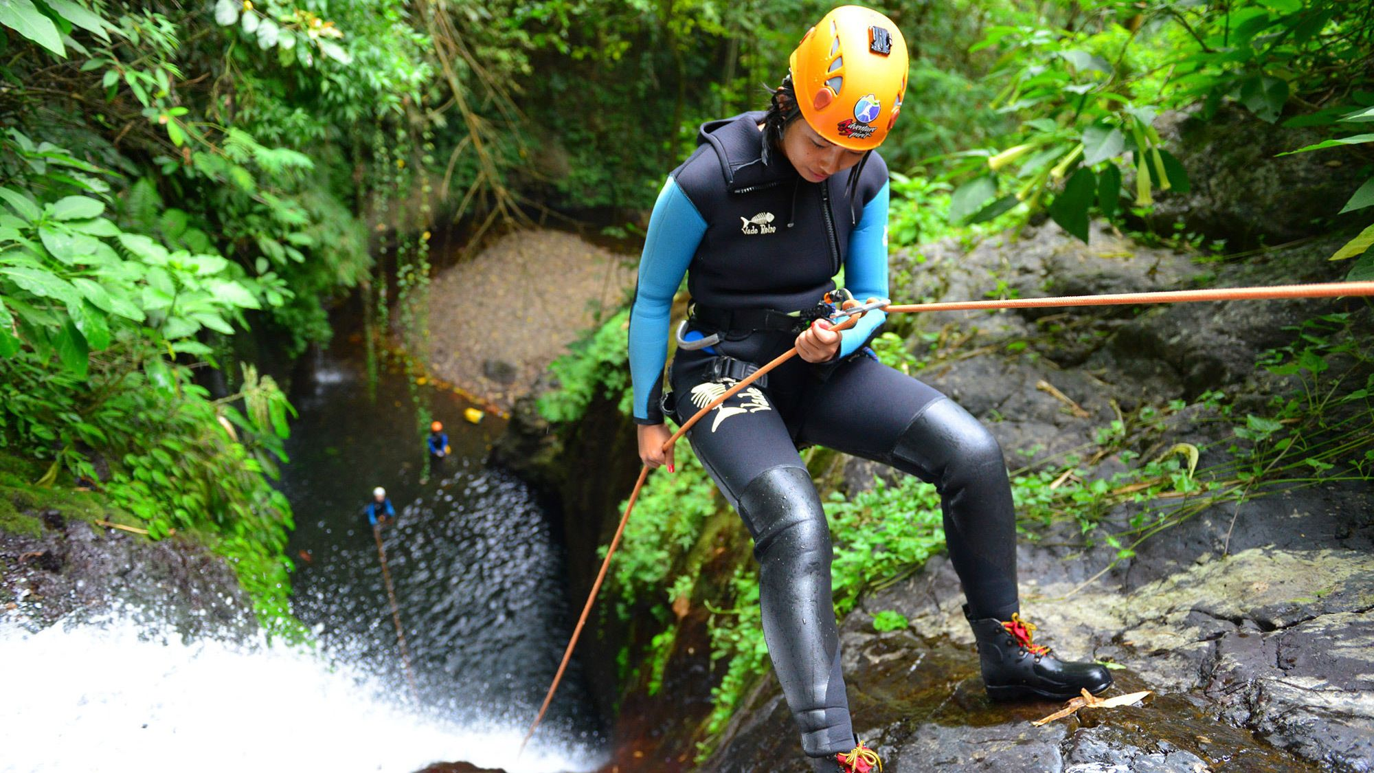 Rock climber holds on to a rope and repels down a waterfall