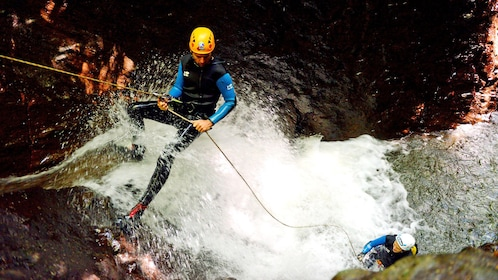 rock climber repels down a waterfall into a pool