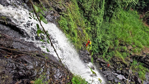rock climbers repels down a waterfall into a pool