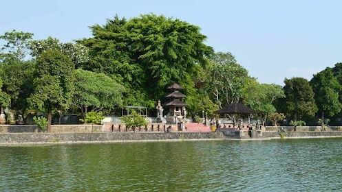 A temple with a stone wall on the water in Indonesia