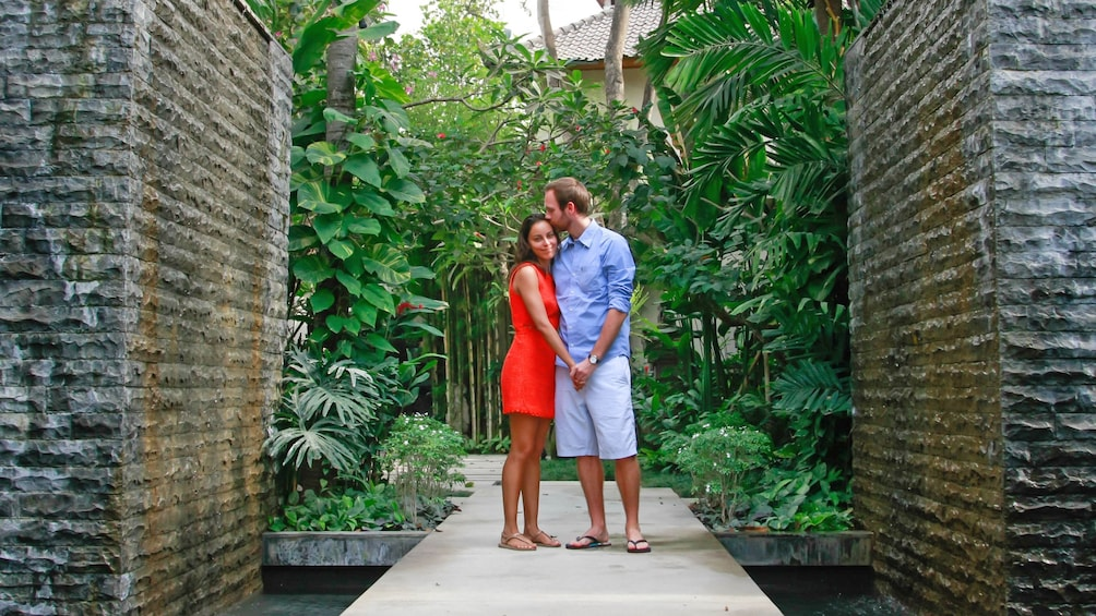 A man and woman stand between brick walls in a bamboo garden
