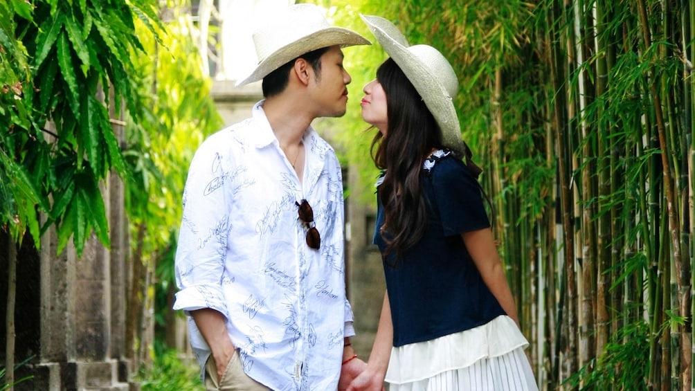 A man and a woman are about to kiss in a bamboo garden