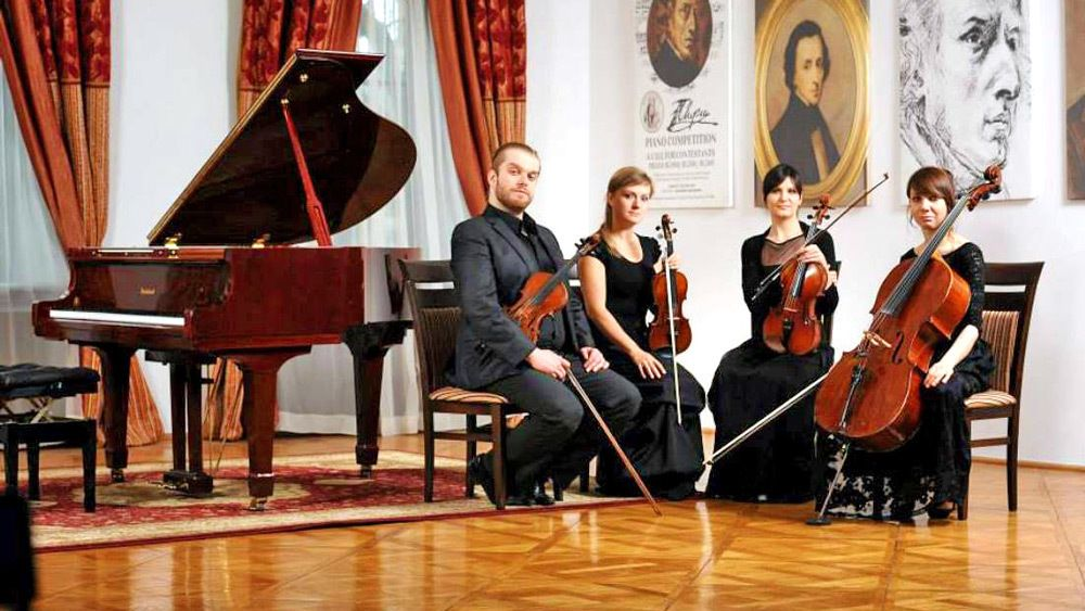 A string quartet poses next to a baby grand piano