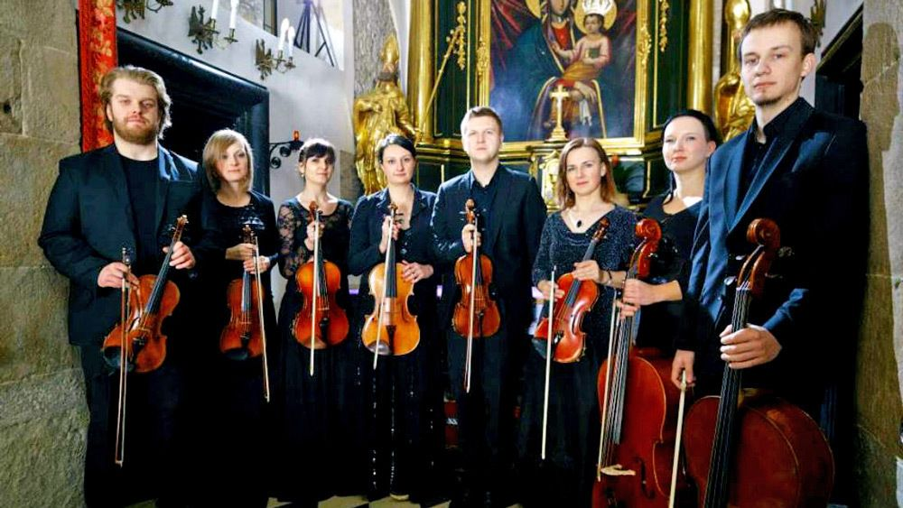 A violin octet poses for a photo
