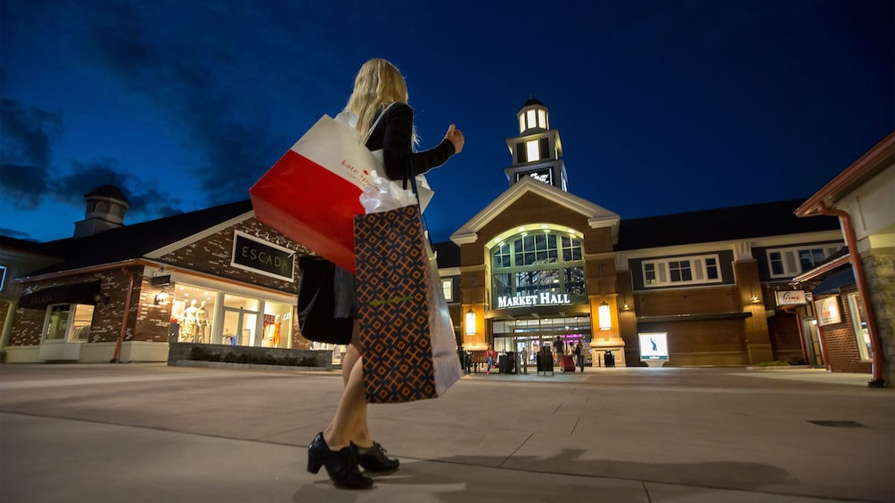 Woman with shopping bags at outlet mall at night in New York