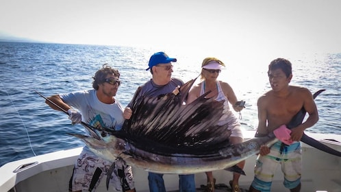 Tourist group posing with large exotic fish that has been caught.
